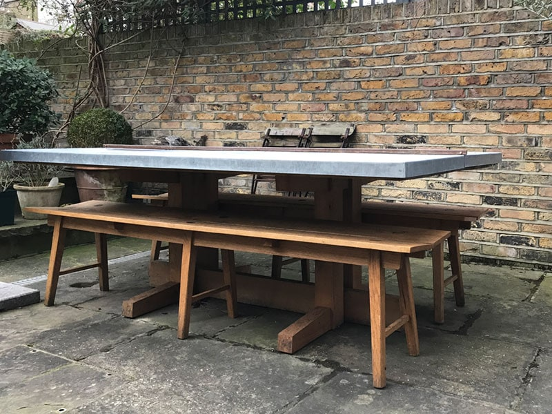 Solid French oak outdoor dining table with Zinc overwintering protective top pictured with butterfly benches handmade by HB Studios