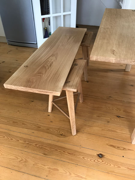 Detail of a pair of bespoke made to order handmade stools which transform into a bench using the central table leaf of an extending handmade oak dining table.
