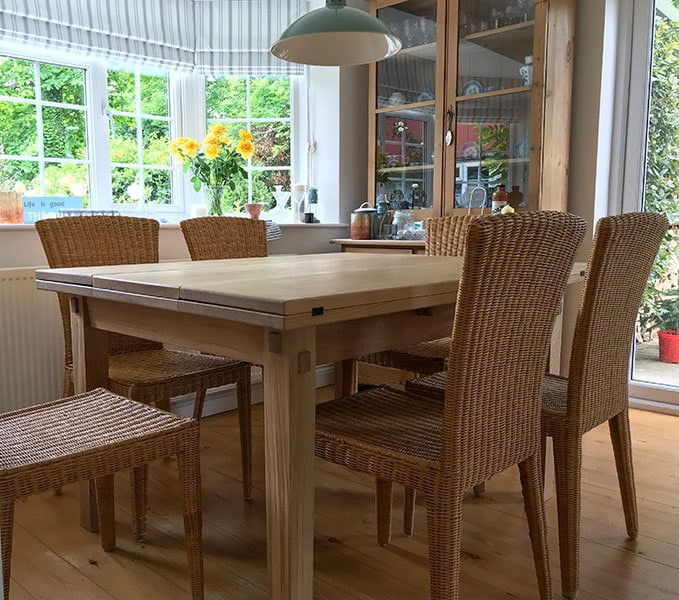 A beautiful handmade extending oak dinging table in a kitchen setting surrounded by high back wicker dining chairs.