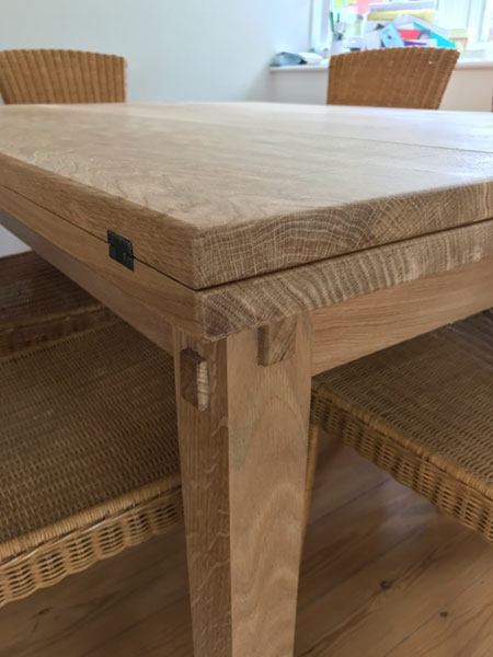 Top end detail with black metal hinges of a bespoke made to order handmade extending oak table when it is folded in compact position
