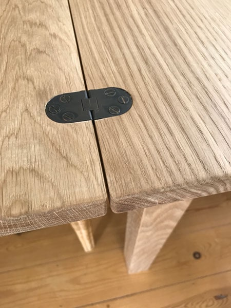 Top detail with black metal hinges of a bespoke made to order handmade extending oak table when it is in it's extended position