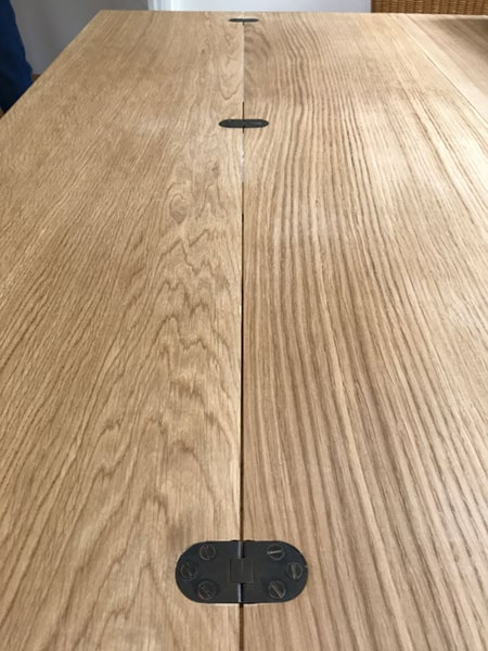 Top detail with black metal hinges of a bespoke made to order handmade extending oak table when it is opened and extended.