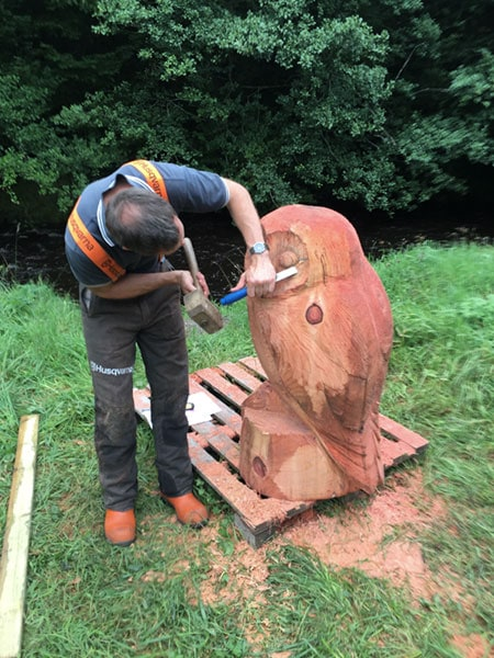 Patrick Bateman carving with a chainsaw to create the facial features of a large wooden owl sculpture.