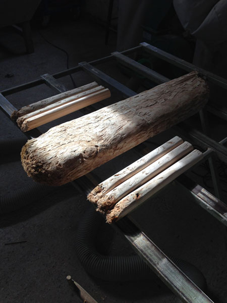 A piece of driftwood sawn in half and then into even strips to make up the legs of a rustic milking stool