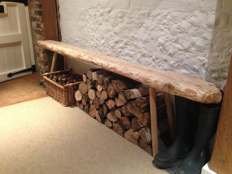 A long hallway bench created from weathered driftwood shown with stacks of chopped up firewood and wellington boots in a cottage hallway.