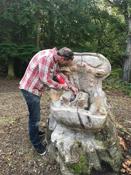 Patrick Bateman of HB Studios tending to a giant hippopotamus sculpture formed from the stump of an old tree at Bedburn sculpture park. He is filling some cracks that have appeared in the mouth of the hippopotamus with foam to protect it from rotting.